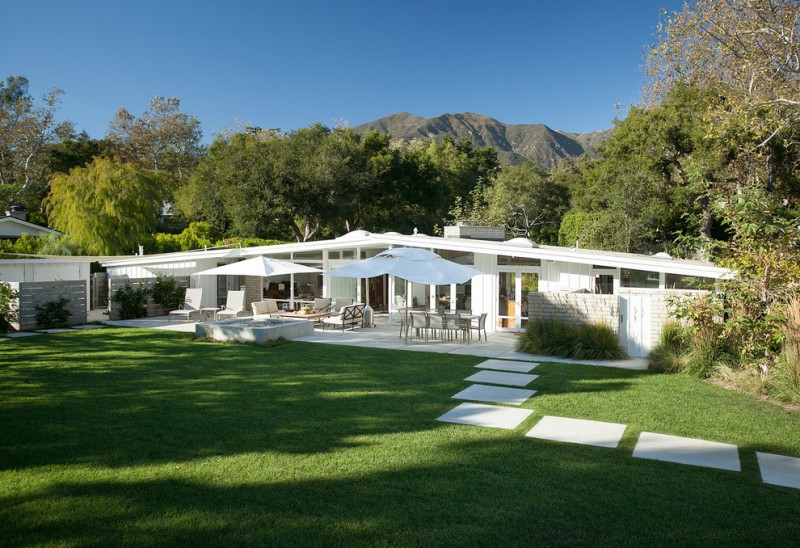 white long mid century homes with large windows, glass door, large patio on the back, thin slanting roof
