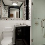 White Small Bathroom With Aquare Tiles, White Toilet, Dark Container, With Sink On Top, Mirror, Bath Area