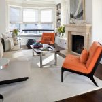 Contemporary Living Room With White Walls And A Standard Fireplace Orange Accent Chairs And Pillow Throws White Rug Medium Toned Wooden Floors