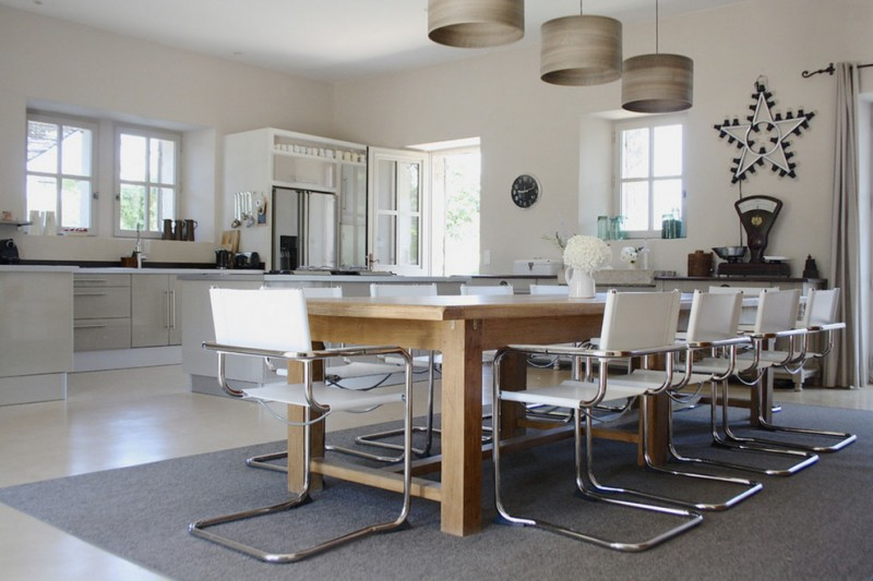 Large trendy concrete floor dining room with white walls pendant lamps wooden table white chairs with metal legs grey rug
