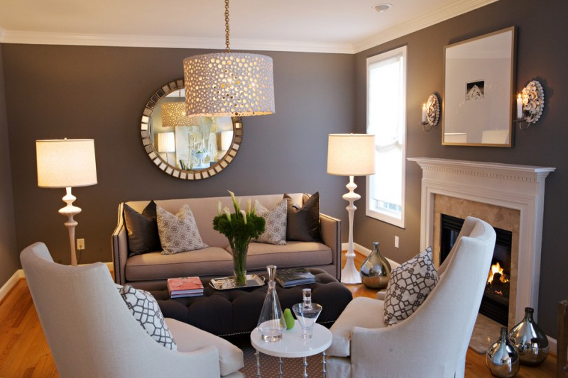 Mid sized elegant medium tone wood floor living room with brown walls and a standard fireplace pendant lamp standing lamp black and white pillow throws gray sofa white accent chairs