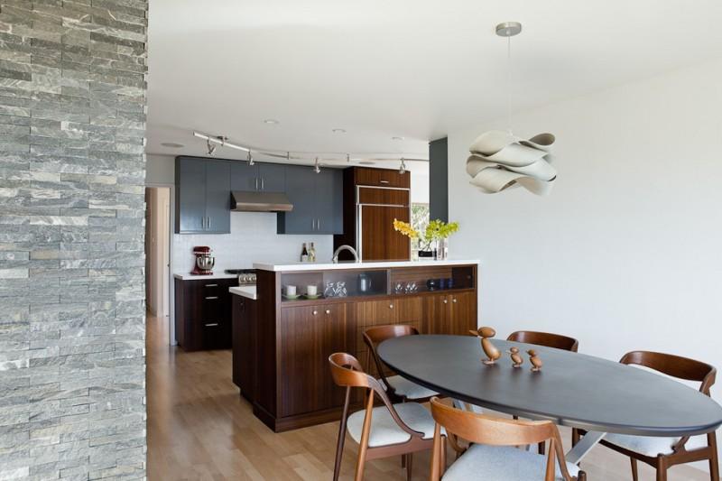 Modern galley light wood floor eat in kitchen with flat panel cabinets, black cabinets, quartz countertops, white backsplash, porcelain backsplash and stainless steel appliances