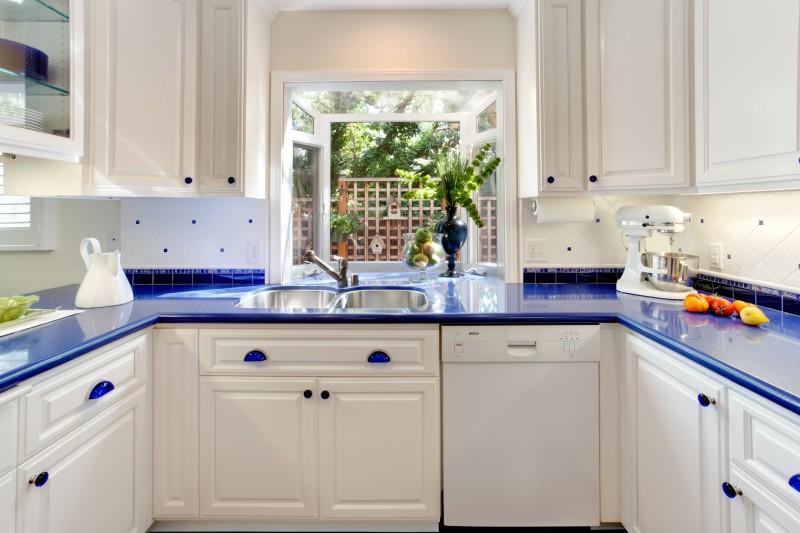 bay window double sink white cabinet white appliances blue countertop blue holder tiled backsplash