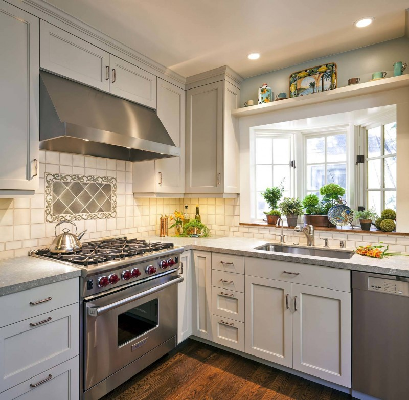 bay window sink white window white cabinet stainless steel appliances tiled wall decorated backsplash recessed lights wood floors