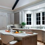 Bay Window White Trim Recessed Lights Flat Panel Cabinet Island Sink Granite Countertop Tiled Backsplash Dining Stools