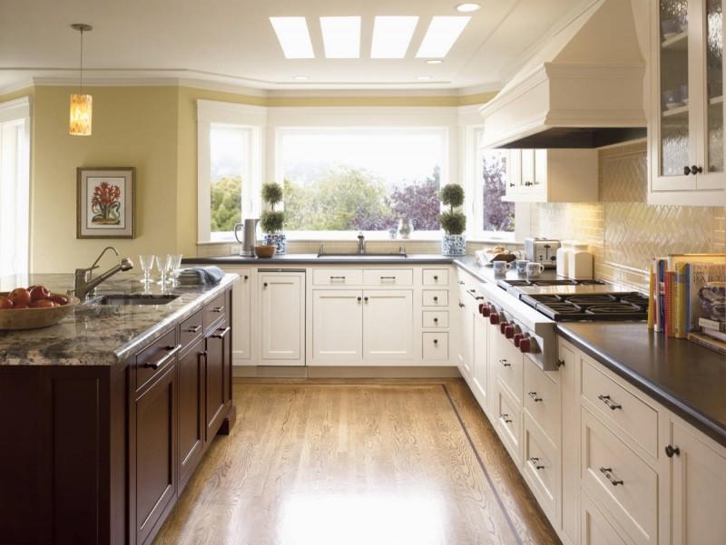 bay window yellow wall sink black countertop granite countertop white cabinet hood  pendant lights tiled backsplash