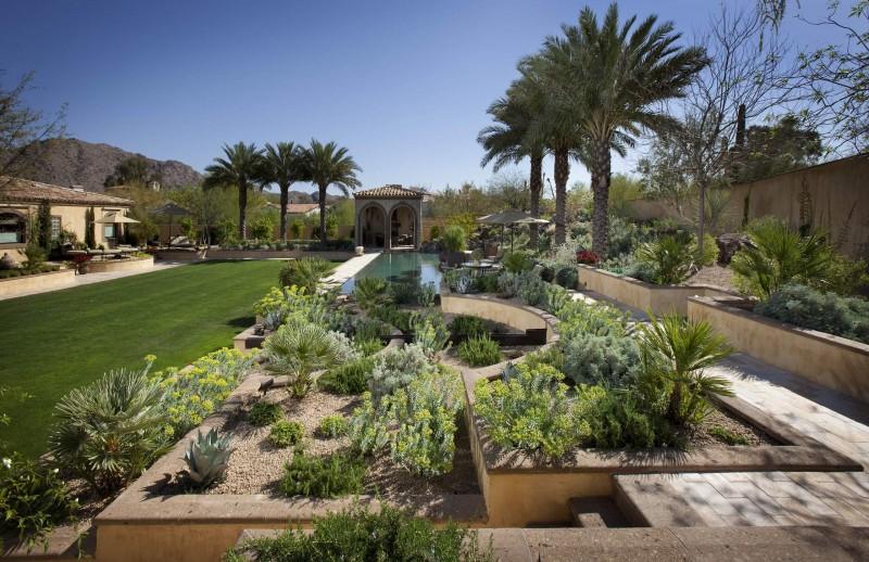 brick paving panters garden wall arched pathway patio umbrella pool patio palm tree grass yard