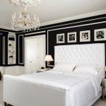 Classic Carpeted Bedroom With Black Walls And White Trim, A Standard Fireplace And A Wood Fireplace Surround Chandelier Lamp Table Lamps Metallic Cabinets