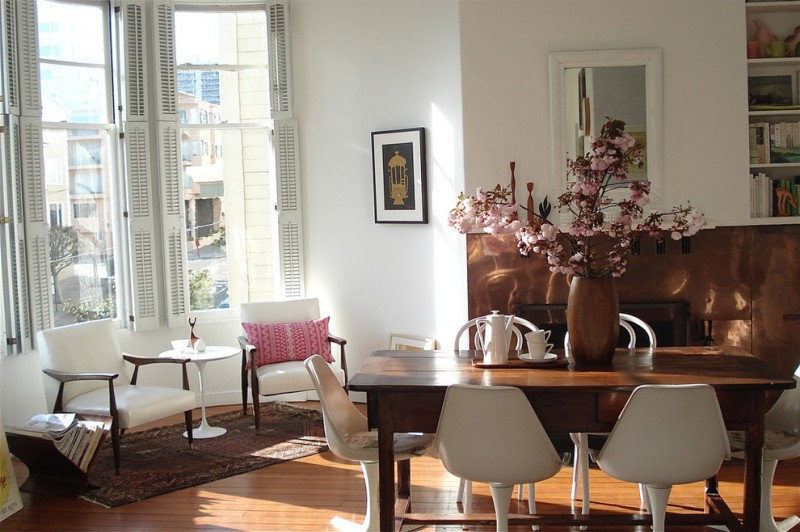 eclectic medium tone wood floor dining room with white walls wooden dining table and white chairs wooden vase brown rug