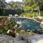 Hot Tub Water Feature Colorful Flowers Boulders Stone Paving Pebble Outdoor Seating Waterfall