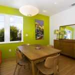 Medium Tone Wood Floor Dining Room With Green Walls Orange Polka Dot Sofa Wooden Table Dining Set Wooden Cabinetry Pendant Lamp