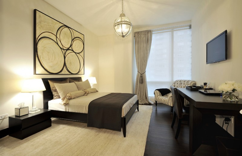 mid sized trendy guest dark wood floor bedroom with beige walls golden art work black table with table lamps pendant lamp mounted TV