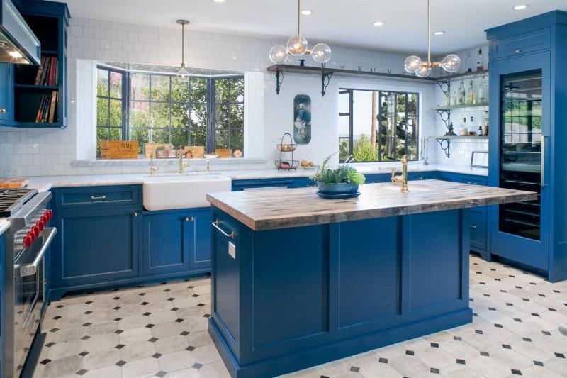 tiled backsplash bay window blue trim blue cabinet floating shelves marble countertope kitchen island sink tiled floor