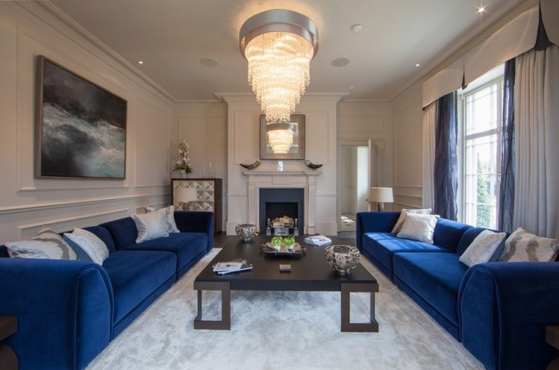blue sofa big chandelier curtains fireplace frame molding gray rug mirrored side table oversized coffee table stone fireplace glass window white molding