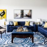 Blue Sofa Blue Pattern Area Rug Brown Armchairs With Cream Cushions Gold Accessories Nesting Tables Side Table Center Table With Cushion