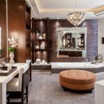 Brown Bathroom Bathtub Brown Ottoman Brown Textured Wall Chandelier Chair Vanity Tray Mirror Sconce Shelves Floor Tile