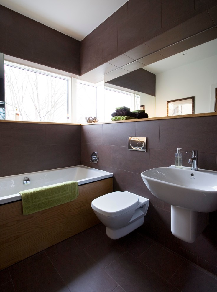 brown bathroom window brown tile floor and wall wide horizontal mirror oversized tub wall mounted sink wall mounted toilet