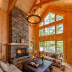 Brown Living Room Area Rug Dark Wood Coffee Table Floor To Ceiling Windows High Ceiling Fireplace Wood Storage Sofas Chandelier