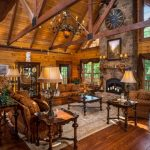 Brown Living Room Ceiling Wood Beams Custom Log Home High Ceilings Reclaimed Wood Rustic Floors Brown Sofas And Armchair Glass Tables With Wood Frame Fireplace Chandelier
