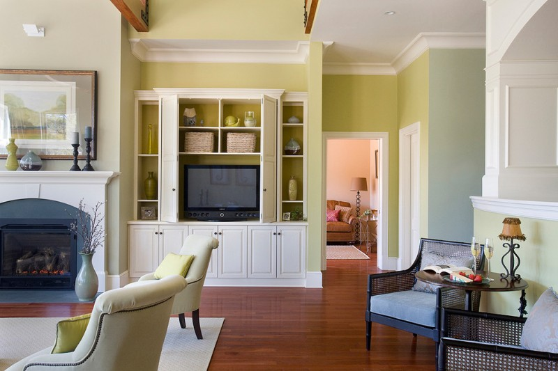 built in tv cabinet area rug crown molding fireplace green painted wall armchairs wood flooring painting side table