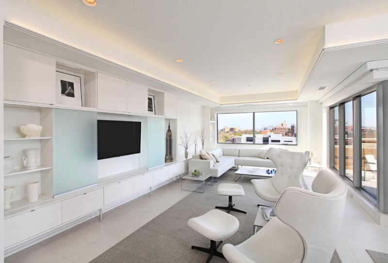 built in tv cabinet beige floor built in shelves cove lighting floor carpet tile frosted glass panels hidden tv cabinet white sofa white chairs footstools