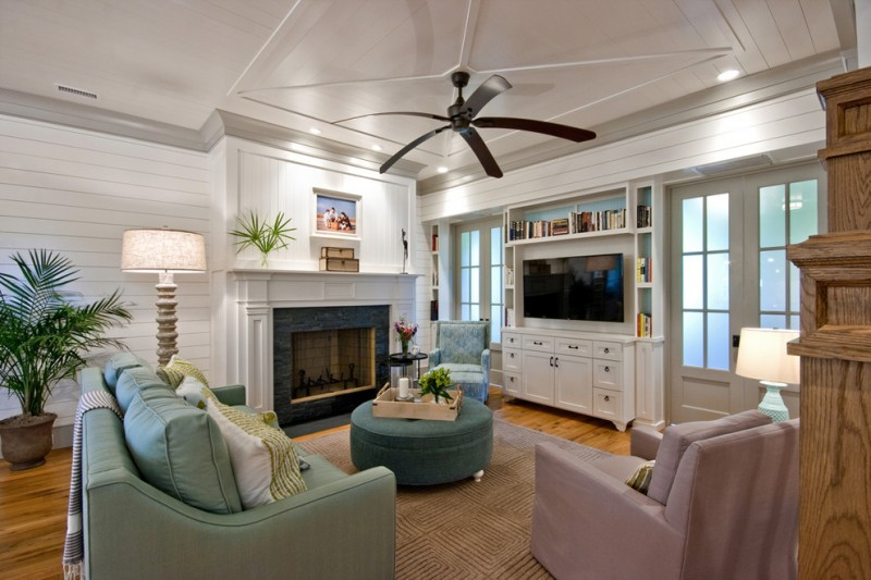 built in tv cabinet black ceiling fan black fireplace surround built in bookcase fireplace green sofa purple armchair ottoman house plant brown area rug