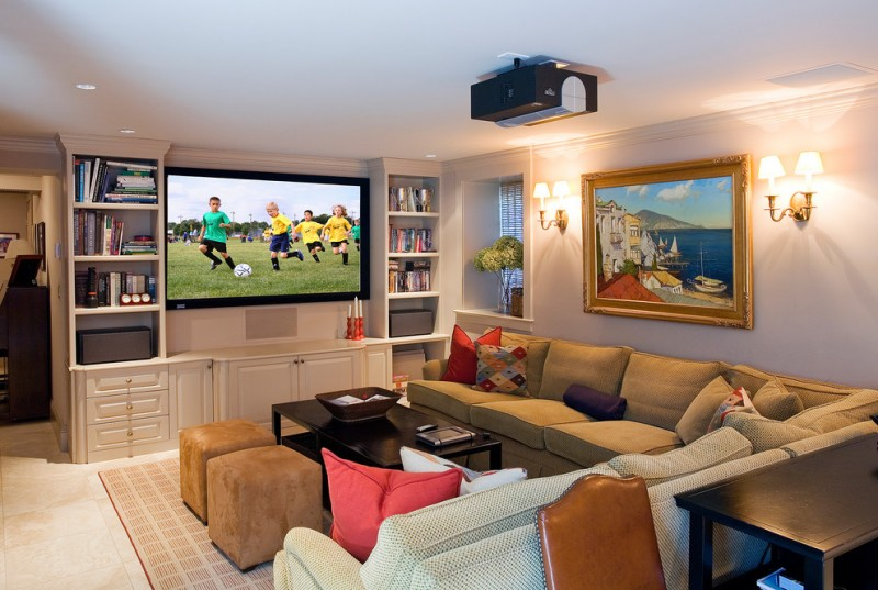 built in tv cabinet brass built in shelves media room painting red accents sconces sectional sofa black table stools pillows