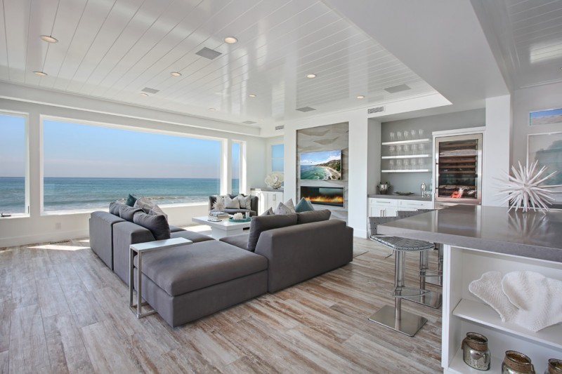 floor couch beach front gray bar stools gray countertop recessed lighting wine refrigerator ceramic flooring with wood pattern white coffee table