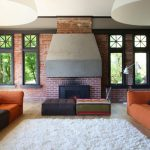 Floor Couch Brick Wall Brick Fireplace Floor Lamps Dome Lights Historic Windows Library Light Wood Floor Orange Couch Shag Rug Steel Hood Striped Couch Striped Ottoman
