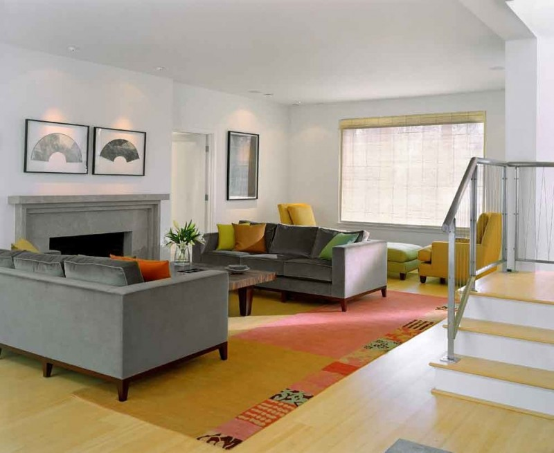 grey sofa wooden coffee table bright floor colourful area rug fireplace wide window with blind yellow armchairs green ottoman