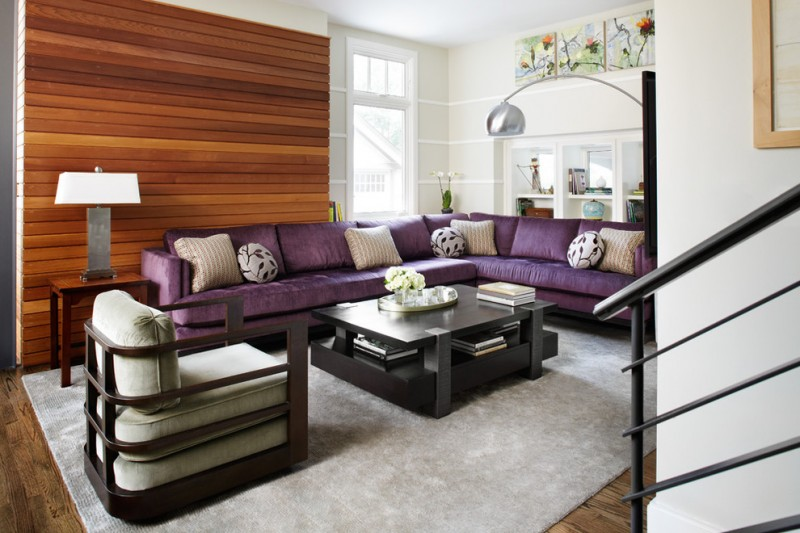 purple sofa armchair beadboard black coffee table floor lamp horizontal wood paneling grey rug steel railing wood floor wooden side table table lamp