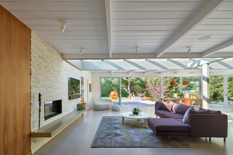purple sofa concrete floors exposed beams fleetwood doors floating mantel large area rug low ceiling purple accent white low coffee table ribbon fireplace