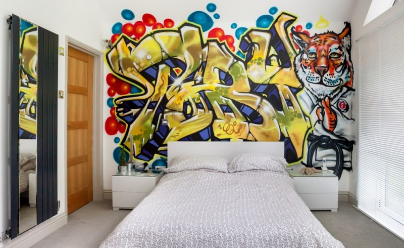 art deco bedroom mural graffitti mirror radiator wood door white bed with patterned bedding white minimalist nightstands white blinds