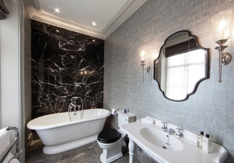black accent wall bathroom mirror gray wall black stone wall black toilet lid recessed lighting antique mirror wall sconces sink tub