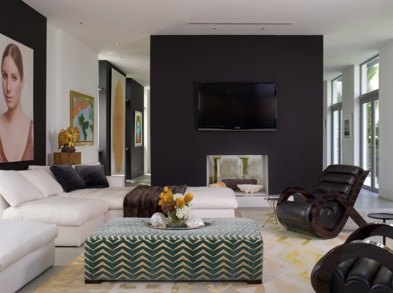 black accent wall beige chaise lounge beige sectional white wall black armchair black fireplace patterned ottoman artwork