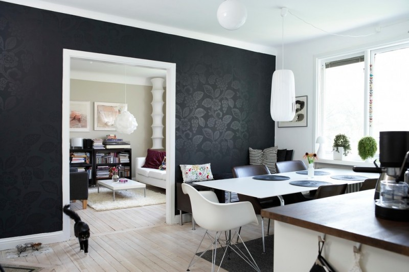 black accent wall black area rug black wallpaper white dining table and chairs white pendant light wood countertop window