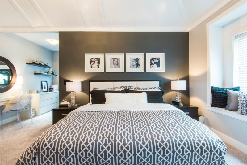 black and white bedding bedroom desk beige carpet black accent wall black throw pillow built in window seat clear table lamp floating shelves