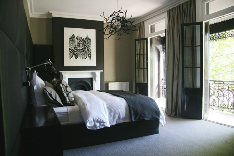 black and white bedding beige wall black and white artwork black chandelier black glass door black padded wall black throw pillow black wall black wall sconce gray carpet iron railing