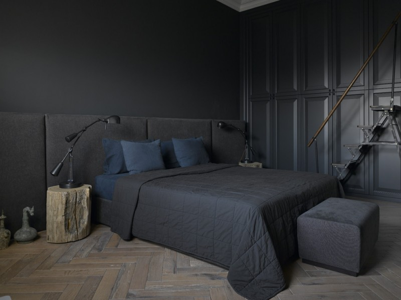 black bedroom black small bench black blanket black stairs black wall blue pillows black hardwood herringbone floor black table lamps
