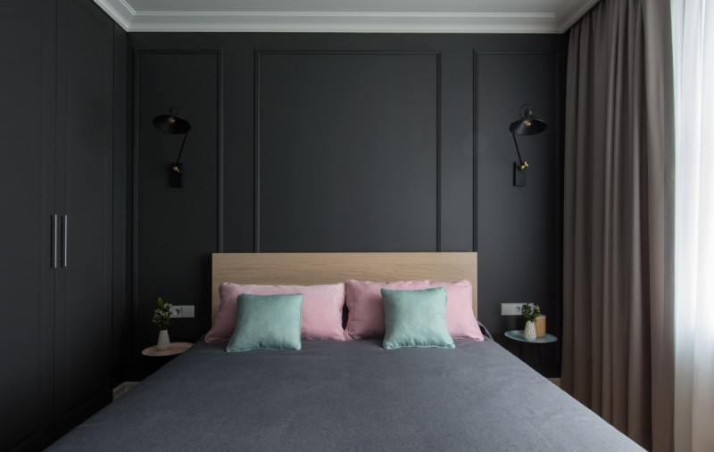 black bedroom black wall mounted lamps small round side tables wooden headboard beige curtains pink and blue pillows grey bed cover