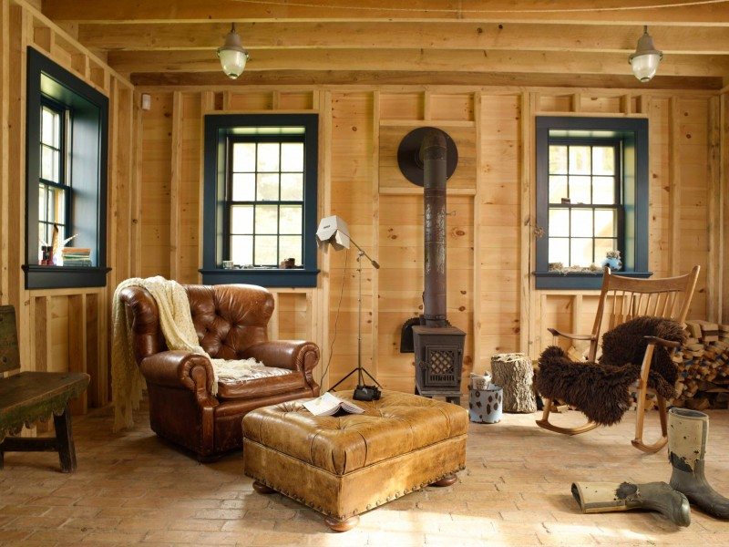 brick floor wood wall black trims exposed beams leather couch ottoman rocking chair wood burning stove ceiling lights