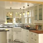 Corner Sink Cabinet Apron Sink Butcher Block Counter Stools Frame And Panel Kitchen Island Pendant Lights Subway Tile Tile Floor White Painted Wood Black Countertop Windows