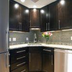 Corner Sink Cabinet Ceiling Lighting Dark Wood Cabinets Granite Countertops Stainless Steel Appliances Tile Backsplash Tray Ceiling Under Cabinet Lighting Wood Floor