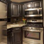 Corner Sink Cabinet Dark Wood Cabinets Floral Arrangement Granite Countertops Kitchen Hardware Stainless Steel Appliances Subway Tiles Dark Tile Backsplash