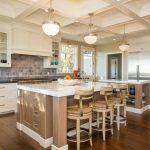 Double Island Kitchen Unique Barstools Wood Flooring Dark Grey Backsplash Light Pendants White Marble Countertops Light Brown Kitchen Island