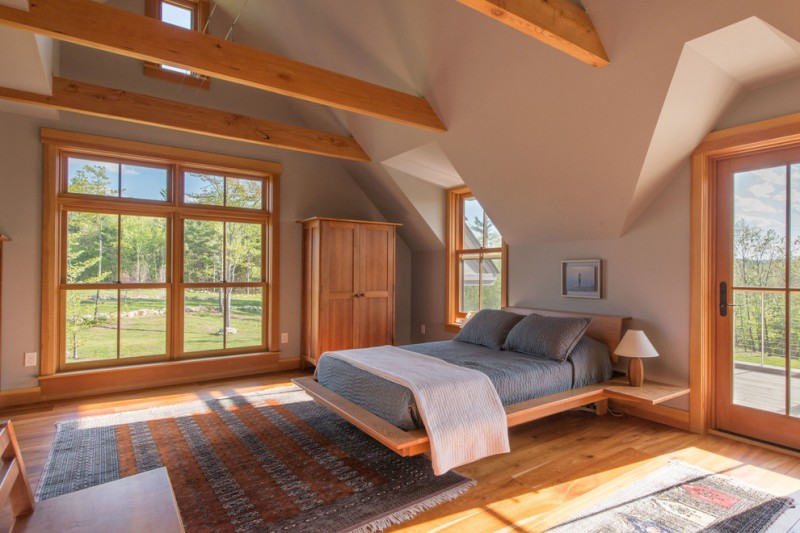 exposed beams high ceiling wooden floor wooden bed floating table area rug gray wall