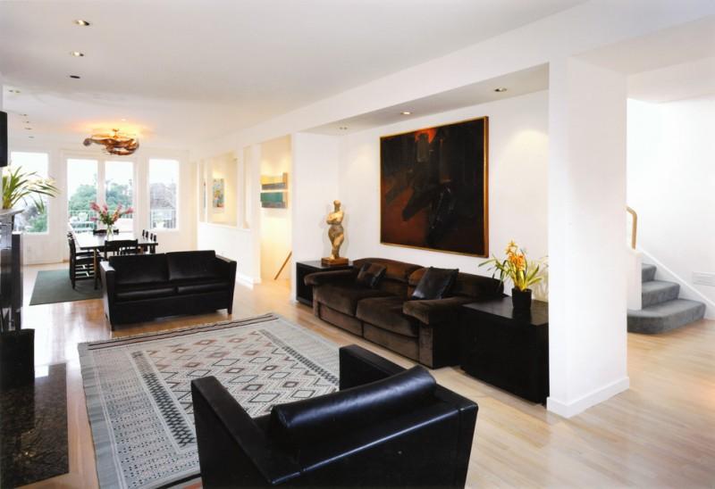 floor sofa black armchair black sofa patterned rug wood floor dark painting chandelier dining table and chairs glass windows