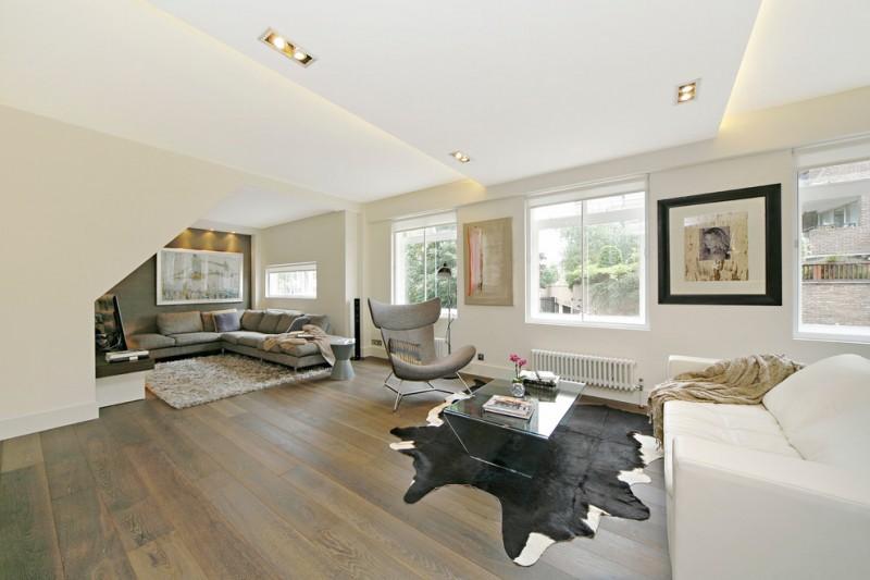 floor sofa grey and white sofas cowhide rug coffee table chair paintings wood floor windows recessed lightings fluffy rug