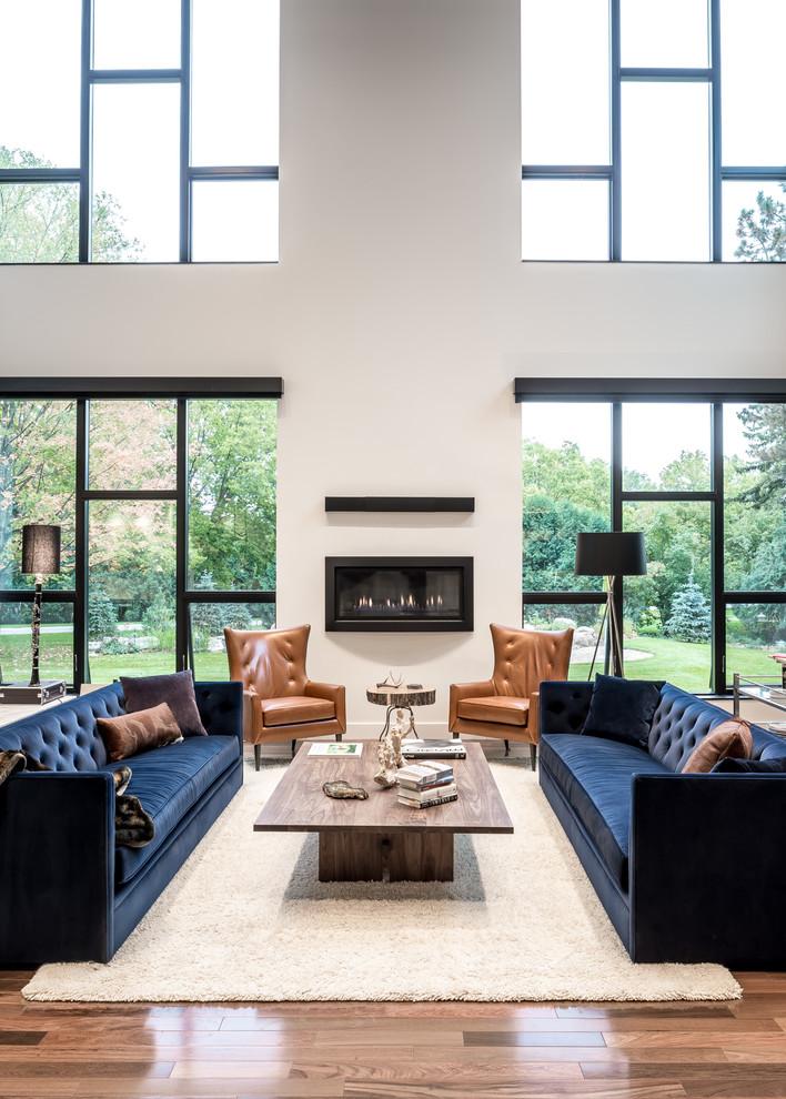 floor sofa wood coffee table white area rug black floor lamp leather armchair windows wood floor glass windows fireplace