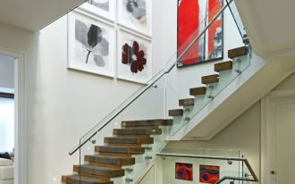 glass stair railing artwork black and white flowers painting red painting wood stairs big round grey ottoman marble black and brown floor